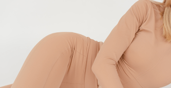 Women experiencing pre-menstrual cramps lies on her side against a white background.