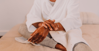 Black person wearing a white robe rubbing lotion onto their arms.