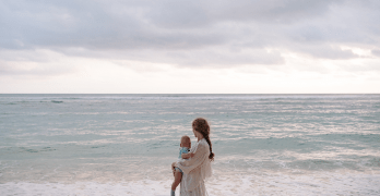 A white woman carrying a baby looks out onto an overcast horizon over the ocean.